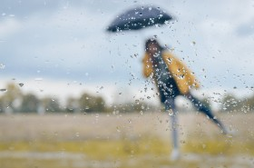 Woman standing under umbrella with raindrops on window glass for